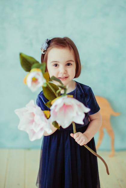 La petite fille garde les fleurs dans la chambre Photo gratuit
