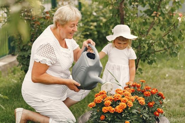 Petite Fille Avec Grand-mère Senior Jardinage Dans Le Jardin. Enfant Au Chapeau Blanc. Photo gratuit