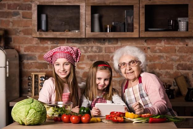 Petite-fille et grand-mère avec tablette, recette de recherche Photo Premium