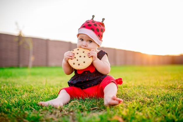 Petite fille avec un gros biscuit au chocolat sur la cour arrière Photo gratuit