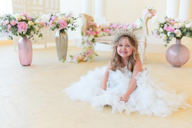 Petite fille habillée comme une princesse se trouve parmi les fleurs dans la chambre Photo gratuit