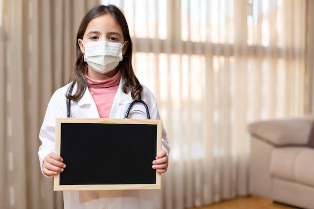 Petite Fille Habillée En Médecin Et Masque Médical Tenant Avec Ses Mains Un Tableau Noir Photo Premium