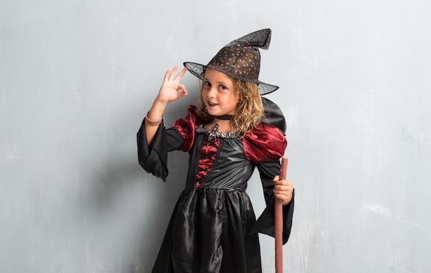 Petite fille habillée en sorcière pour les vacances d'halloween et faisant signe ok Photo Premium