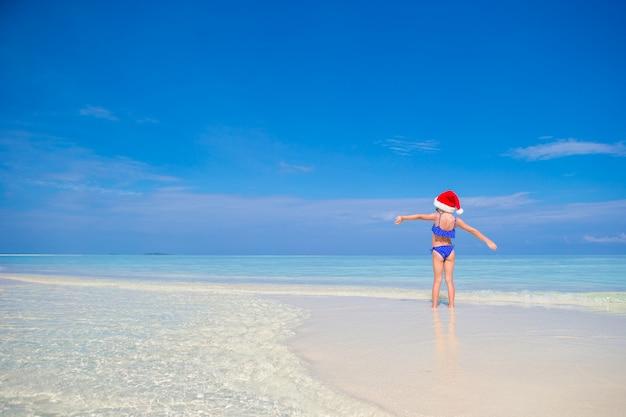 Petite fille heureuse au bonnet de noel pendant les vacances à la plage aux maldives Photo Premium