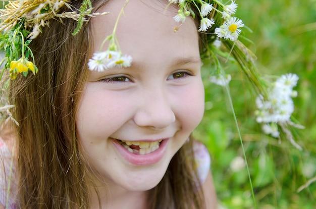 Petite fille heureuse dans une guirlande de fleurs des champs dans le pré Photo Premium