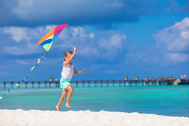 Petite fille heureuse jouant avec cerf-volant sur une plage tropicale Photo Premium