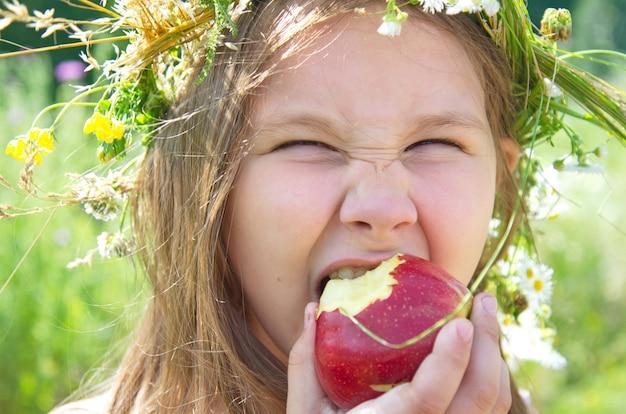 Petite fille heureuse mange une grosse pomme rouge un jour d'été Photo Premium