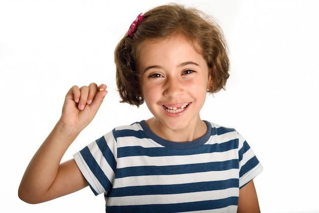 Une petite fille heureuse montrant sa première dent tombée. Photo gratuit