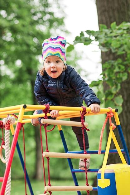La Petite Fille Jouant à L'aire De Jeux Extérieure Photo gratuit