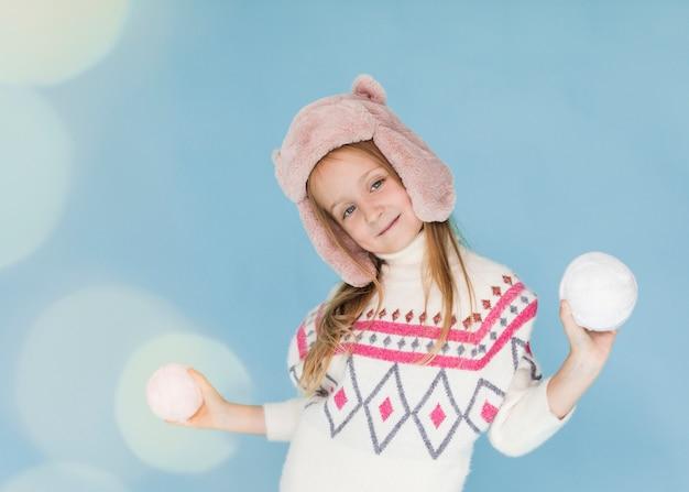 Petite fille jouant avec des boules de neige Photo gratuit