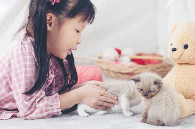 Petite fille jouant avec un chat à la maison, notion de navire ami. Photo Premium