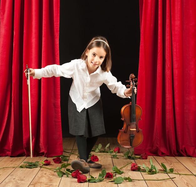 Petite fille jouant du violon sur le théâtre Photo Premium