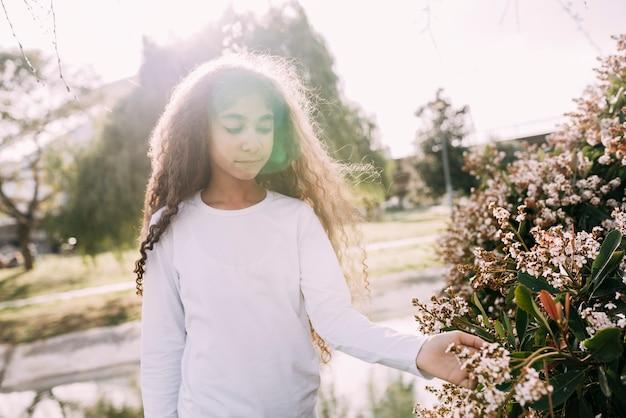 Petite fille jouant avec des fleurs dans le jardin Photo gratuit