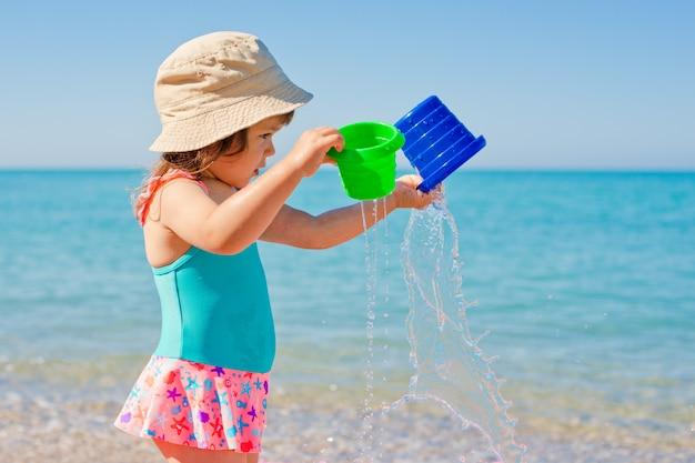 Petite fille jouant avec des jouets en vacances à la plage Photo Premium
