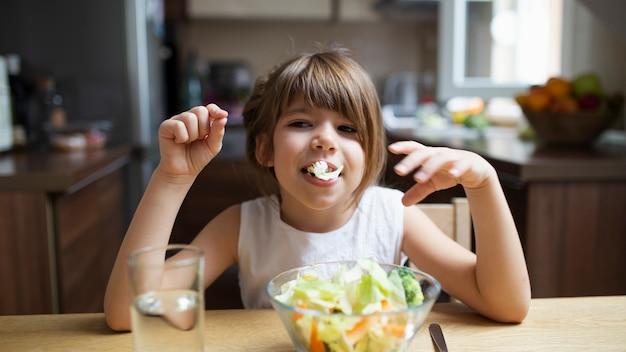Petite fille jouant avec une salade en mangeant Photo gratuit