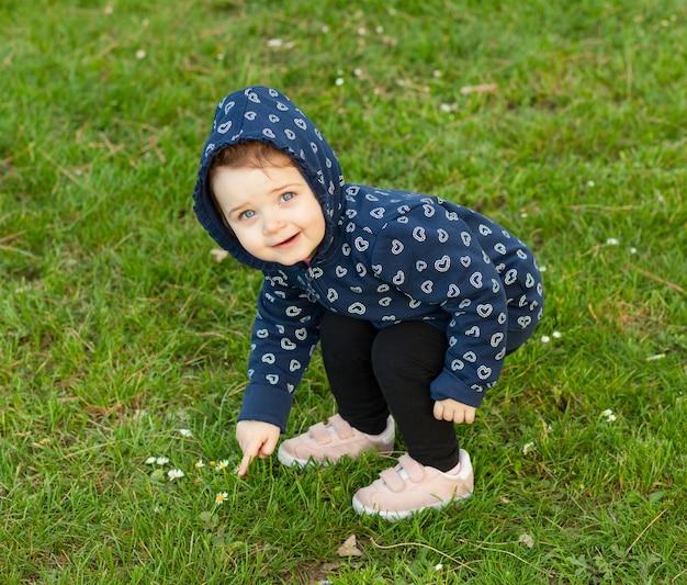 Petite fille joue dans le parc et collectionne des marguerites Photo Premium