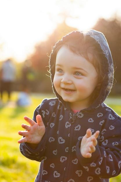 Petite fille joue dans le parc en contre-jour. Photo Premium