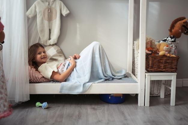 Petite fille joue dans un petit lit avec des jouets, en temps réel Photo Premium