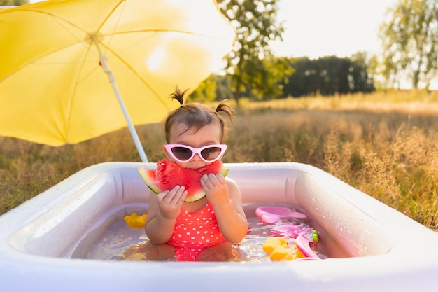 Petite Fille Joue Dans La Piscine Gonflable. Photo Premium