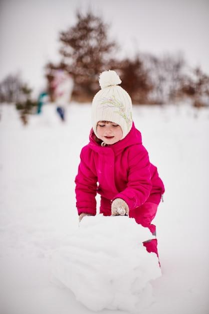 Petite fille joue avec la neige et se réjouit Photo gratuit
