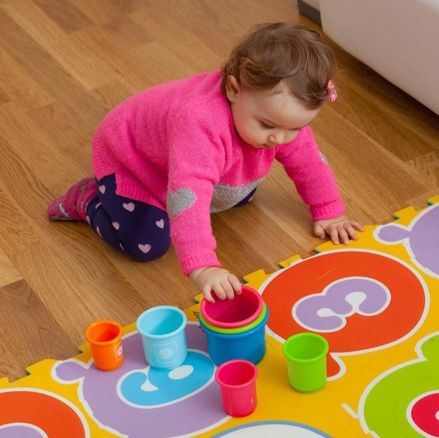 Petite fille joue avec des tasses colorées Photo Premium