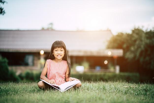 Petite fille lisant un livre dans le jardin de la maison Photo gratuit