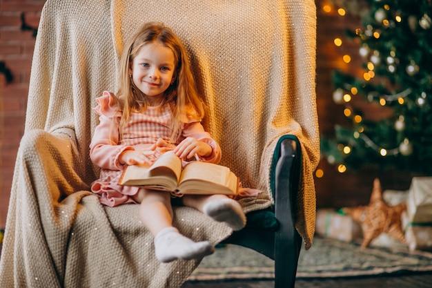 Petite fille avec un livre assis sur une chaise près d'un arbre de noël Photo gratuit