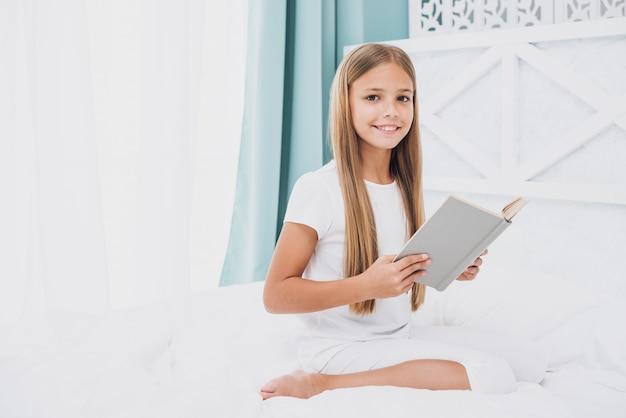 Petite fille avec un livre en regardant la caméra Photo gratuit