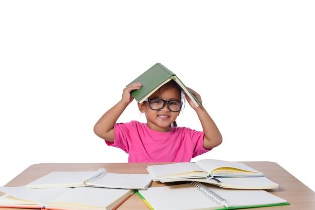 Petite fille à lunettes pensée et beaucoup de livre sur la table. concept de retour à l'école Photo Premium