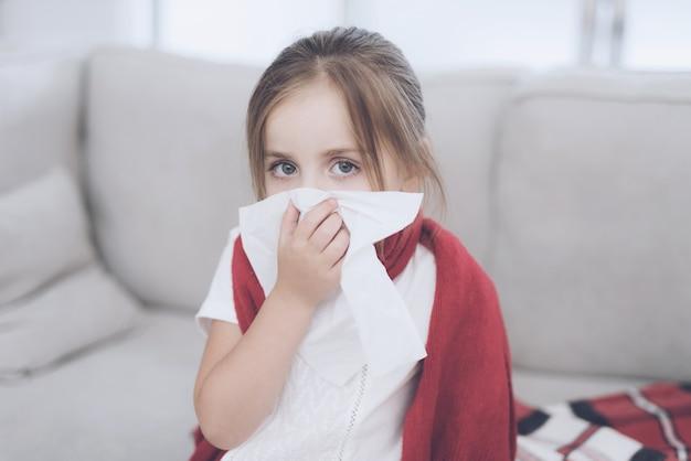 Petite fille malade assise sur un canapé blanc enveloppé dans un foulard rouge Photo Premium