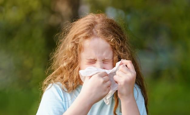 Petite fille malade éternue dans un mouchoir à l'extérieur. Photo Premium