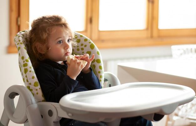 Petite fille mange du pain dans la chaise haute Photo Premium