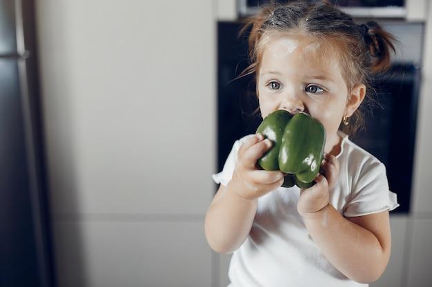 Petite fille mangeant du poivre vert Photo gratuit