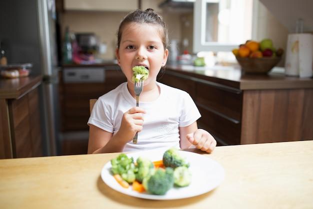 Petite fille mangeant des légumes sains à la maison Photo gratuit