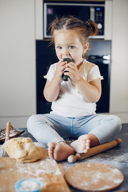 Petite fille mangeant des légumes sur une table recouverte de farine Photo gratuit