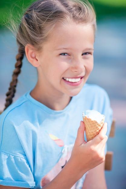 Petite fille, manger des glaces en plein air en été au café en plein air Photo Premium