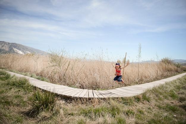 Petite fille marchant sur un chemin de planches de bois dans une zone humide à padul, grenade, andalousie, espagne Photo gratuit