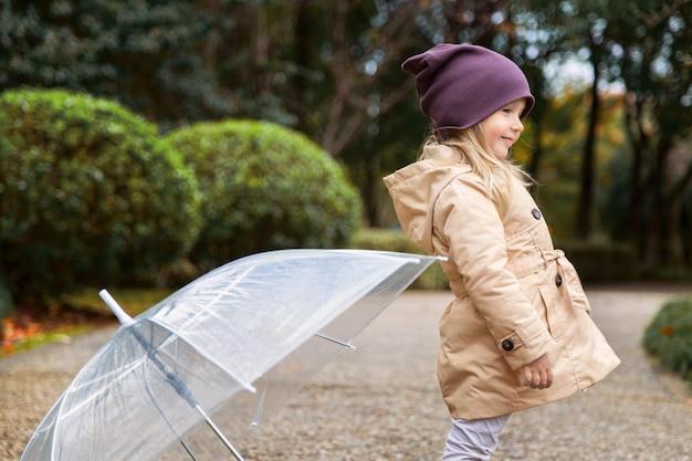 Petite fille marchant dans un parc sous un parapluie pendant une pluie Photo Premium