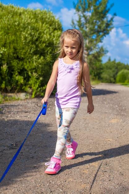 Petite fille marchant avec son chien en laisse Photo Premium