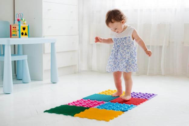 Petite fille marchant sur un tapis de massage Photo Premium