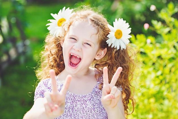 Petite fille avec une marguerite dans ses cheveux montrant le triomphe de la main de paix ou de victoire. Photo Premium