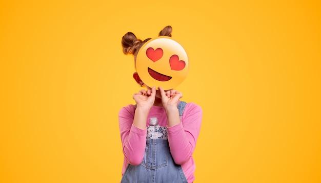 Petite Fille Méconnaissable En Denim Couvrant L'ensemble Du Visage Avec Souriant En Amour émoticône En Se Tenant Debout Sur Fond Jaune Vif Photo Premium