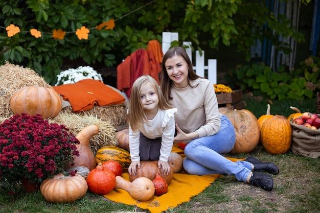 Petite fille et mère profitant de la fête de la récolte au potiron Photo Premium