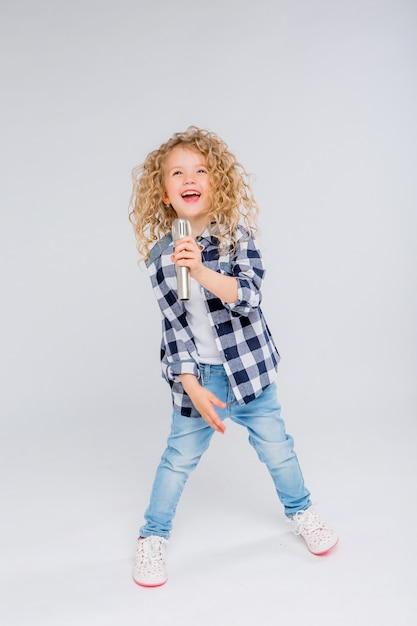 Petite fille avec microphone souriant chantant Photo Premium