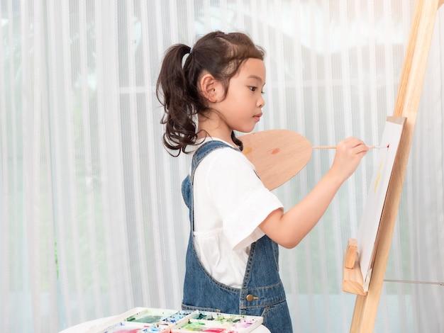 Petite fille mignonne asiatique de 6 ans jouant des aquarelles sur papier blanc. Photo Premium