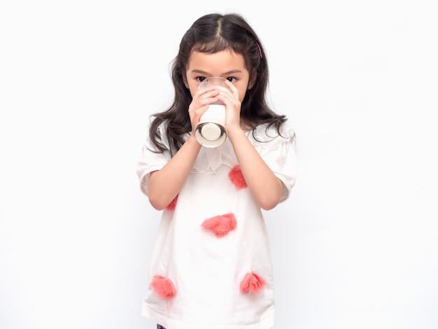 Petite fille mignonne asiatique de 6 ans tenant et buvant du lait dans des verres Photo Premium