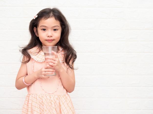 Petite fille mignonne asiatique de 6 ans tenant et buvant de l'eau dans des verres. Photo Premium