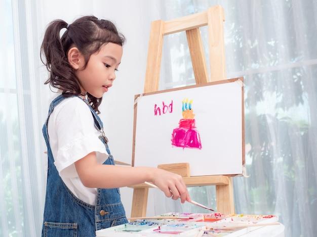 Petite Fille Mignonne Asiatique Jouant Aquarelles Peinture Gâteau Pour Joyeux Anniversaire Sur Papier Blanc. Photo Premium