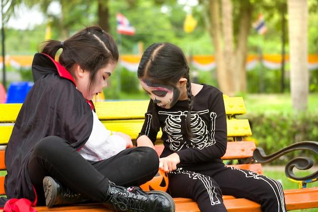 Petite fille mignonne asie en costume d'halloween partage des bonbons et des bonbons en étant assis sur le banc dans la cour de récréation. Photo Premium