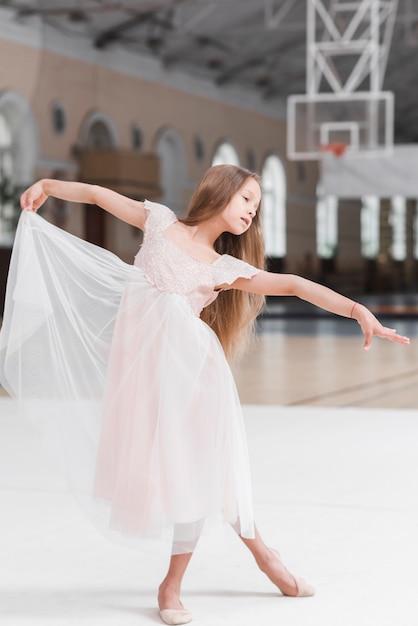 Petite fille mignonne de ballerine dansant sur le sol Photo gratuit